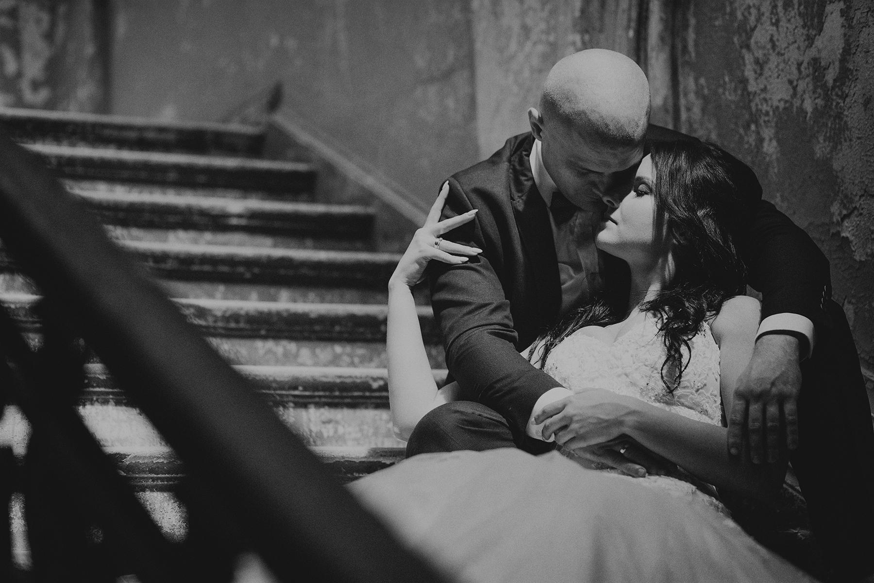 para młoda siedzi przytulona na schodach pałacu w krowiarkach