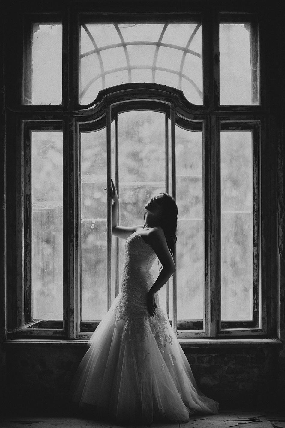 pani młoda pozuje do zdjęcia przy wielkim oknie w pałacu w krowiarkach
