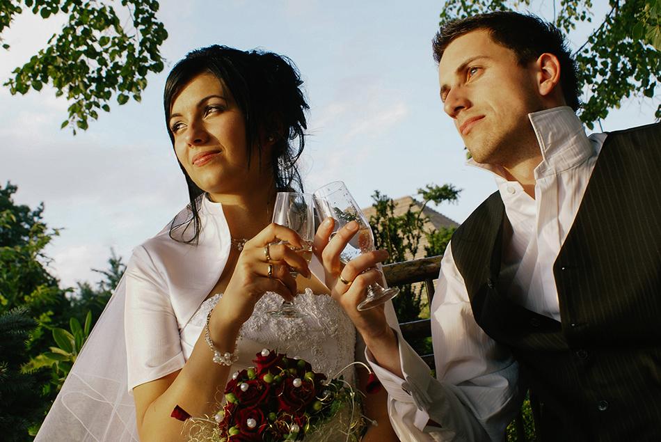 Pierwsze zdjęcia ślubne, para młoda łączy się kiliszkami, patrzy w stronę zachodzacego słońca