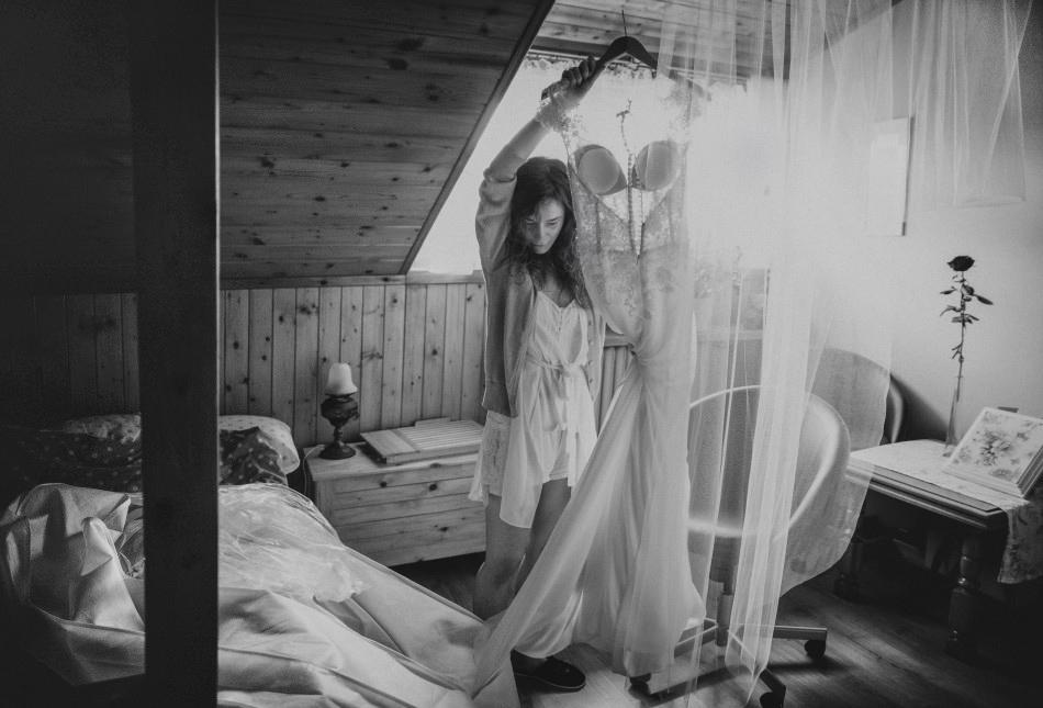 panna młoda przygotowuje się do slubu, trzyma wysoko nad głową suknie ślubną