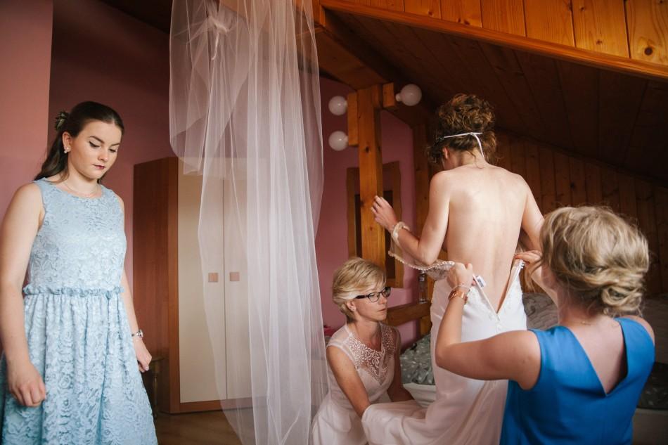 Kobiety ubierają Pannę Młodą, obok stoi zamyślona siostra