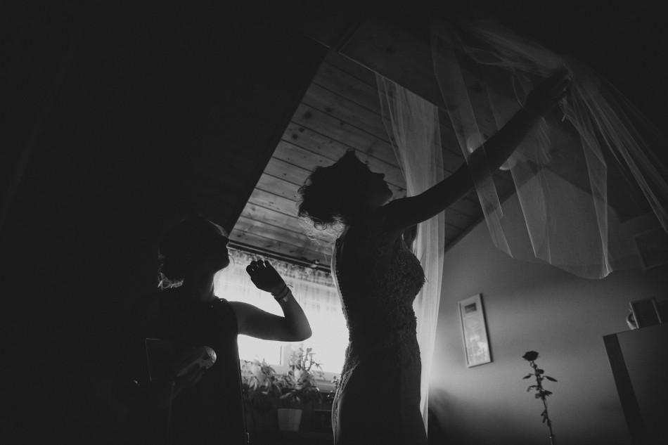 Pani Młoda ściąga welon ślubny z drewnianej belki