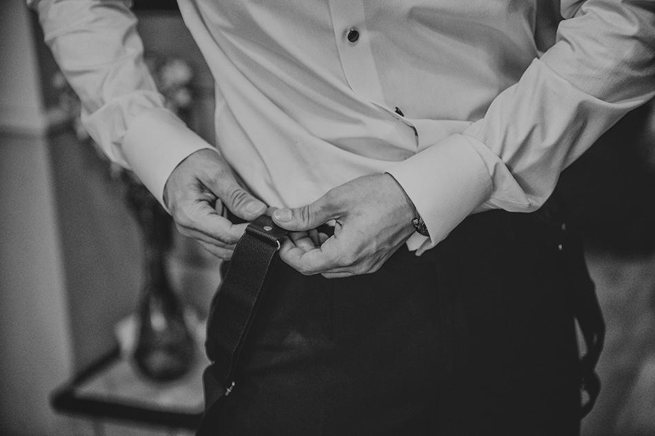 Pan Młody przypina szelki do spodni