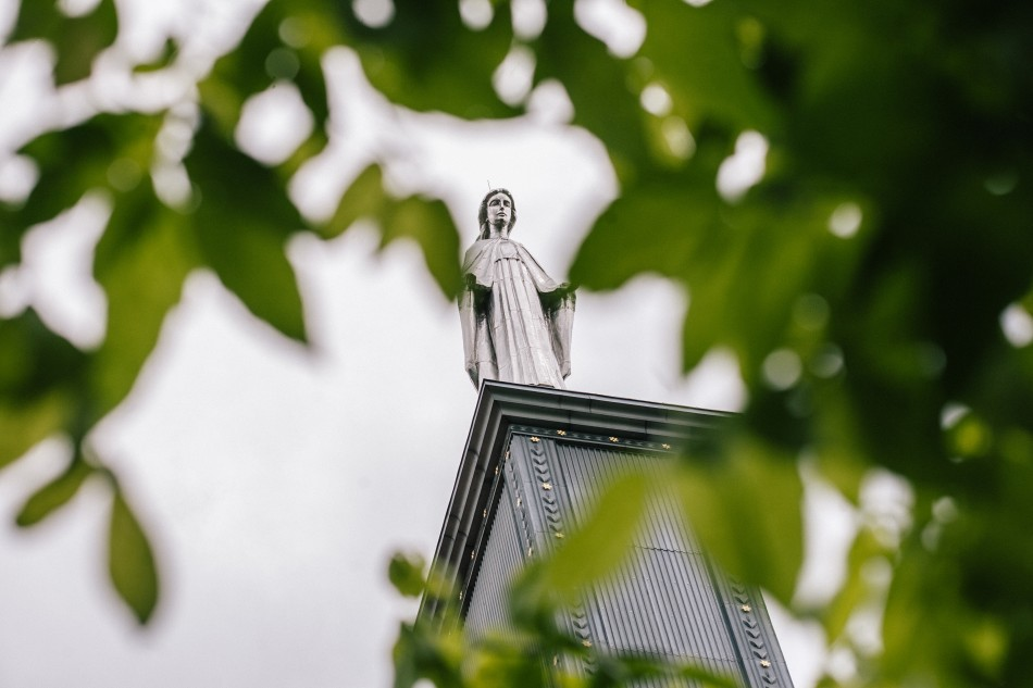 figurka Matki Boskiej postawiona jest na wierzy, prześwituje przez liscie drzew