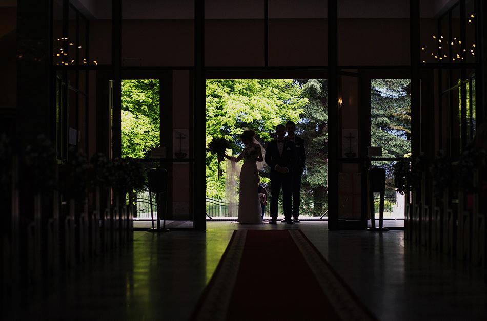 wejście do kościoła, widać ciemne sylwetki pary młodej, na jasnym tle