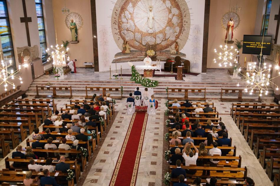zdjęcie z chóru, widać wnętrze kościoła, księdza, parę młodą oraz gości