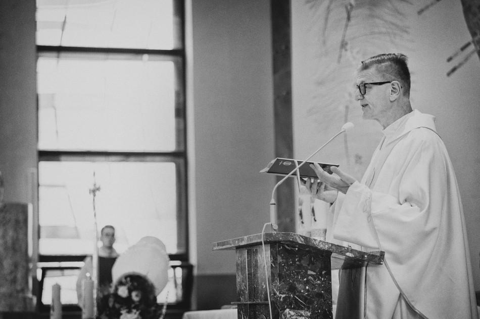 ksiądź podczas kazania unosi pismo święte do góry
