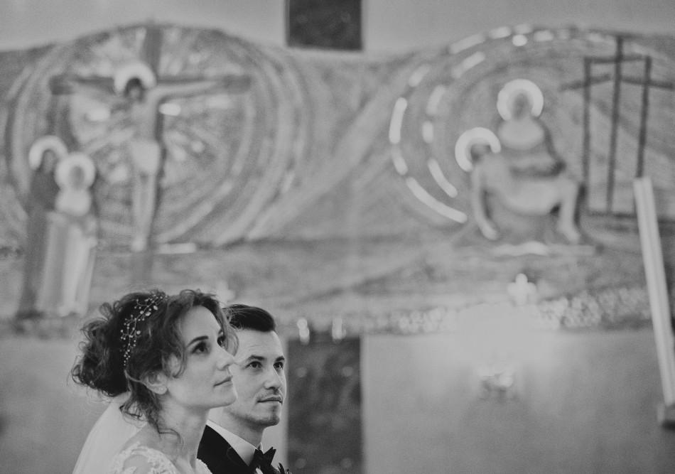 państwo młodzi słuchają kazania ślubnego, nad ich głowami są chrześcijańskie rysunki