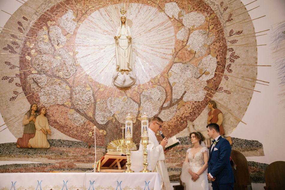 młoda para stoi obok księdza przed ołtarzem