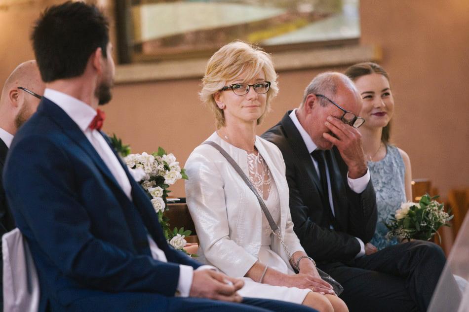 świadek spogląda na mamę Pani Młodej, ojciec opuszcza głowę, siostra śmieje się wesoło