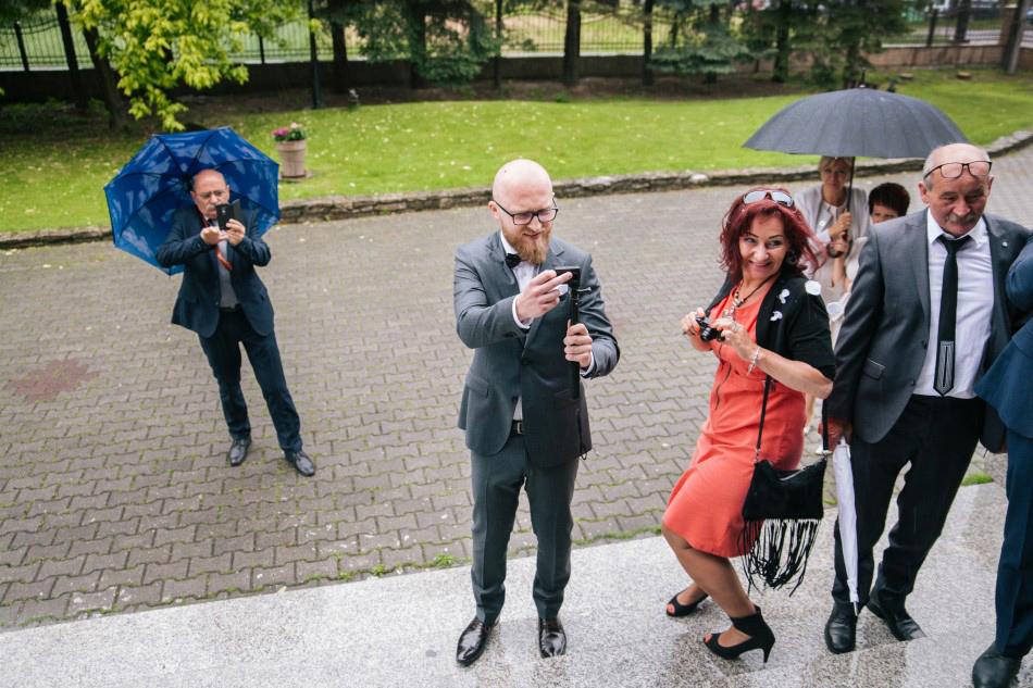 przed kościołem goście oczekują pary młodej, robią im zdjęcia