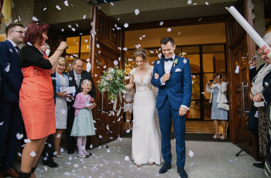 Para Młoda wychodzi z kościoła, goście zasypują ich płatkami róż