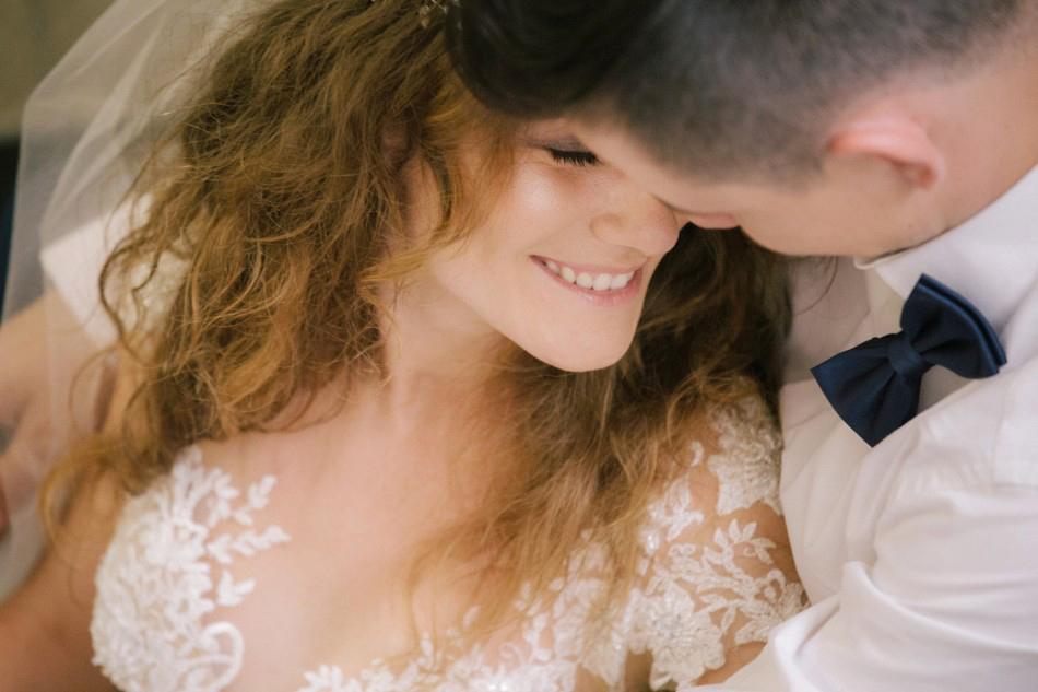 pani młoda uśmiecha się po męża, przytula do niego twarz podczas portretowej sesji ślubnej