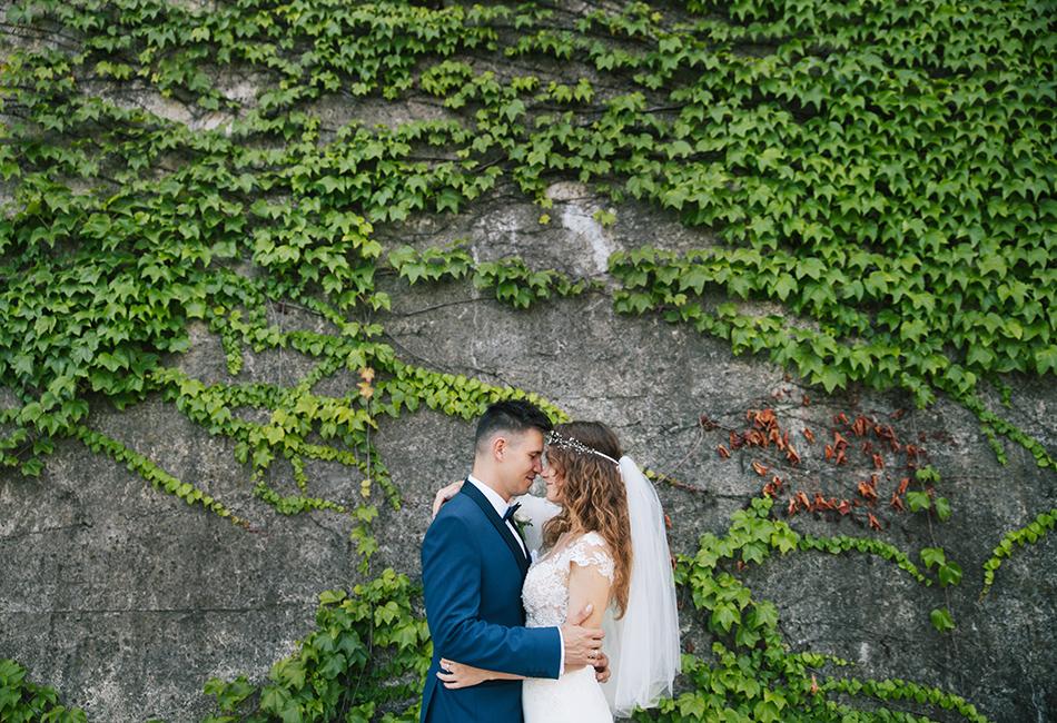 para młoda stoi przytulona do siebie po murem w bielsku-białej, otacza ich bluszcz