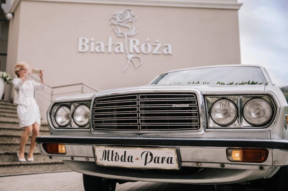 para młoda przyjeżdza na salę weselną do białej róży, matka weselna oczekuje ich z aparatem w ręku