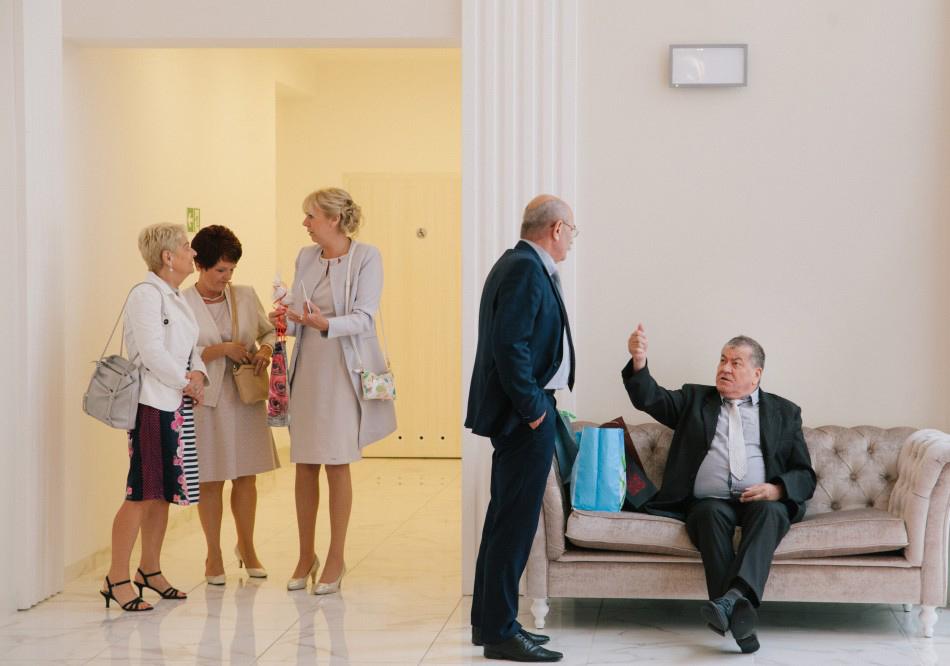 goście weselni oczekują pary młodej, rozmwiaja i gestykulują