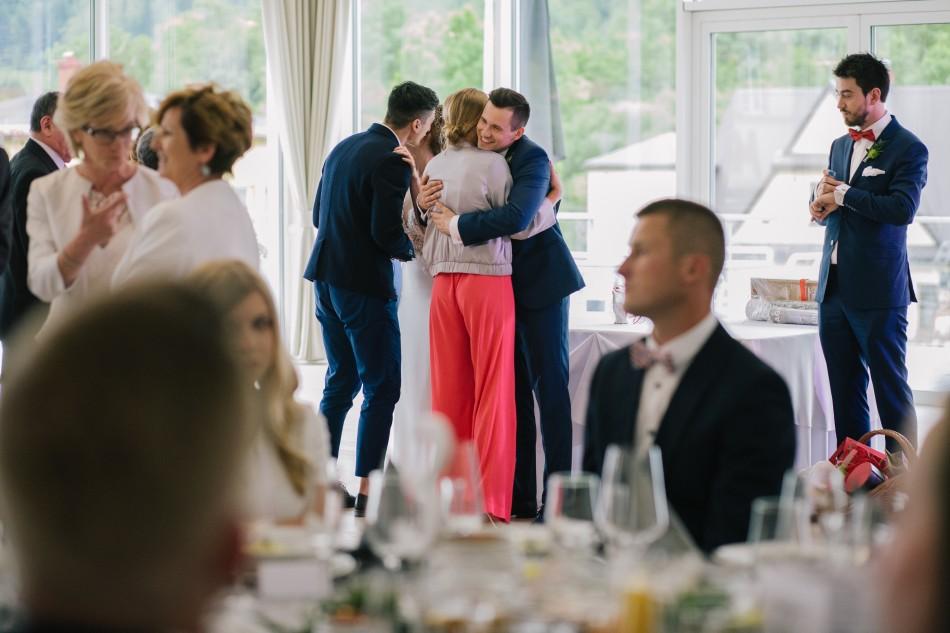 pan młody jest przytulany przez młoda kobietę