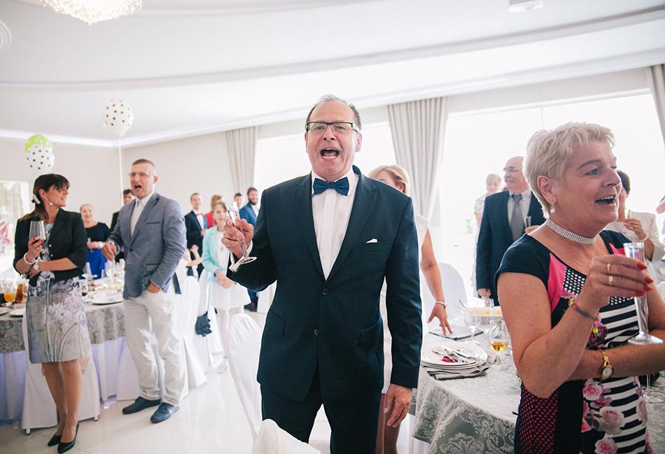 toast weselny, ojciec pana młodego dumnie śpiewa i uśmiecha się razem z innymi gośćmi
