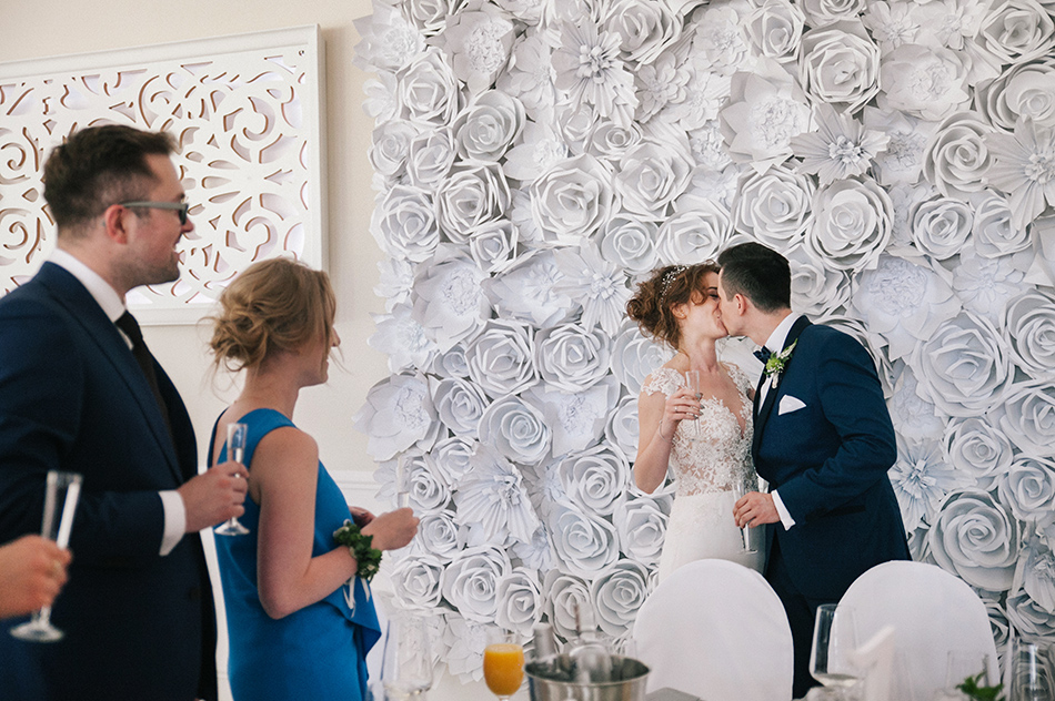 para młoda całuje się pod salą z deroracją z róż