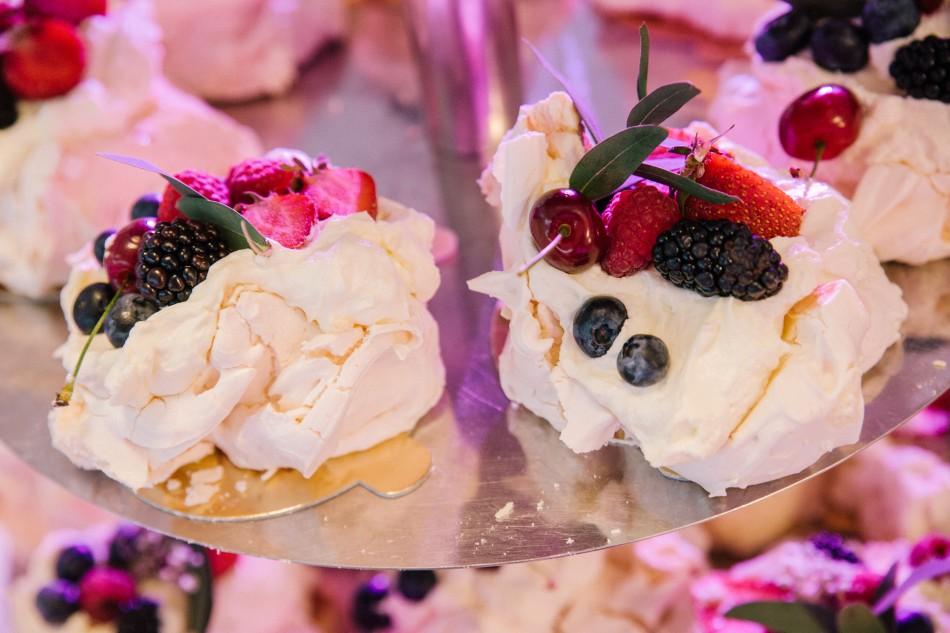 na talerzach leżą słodkie bezy w owocami