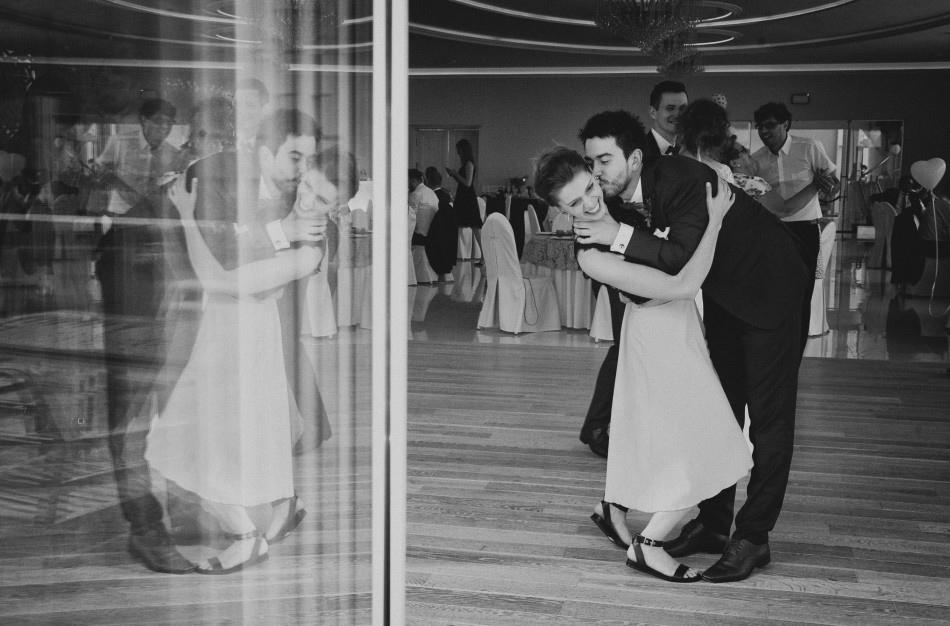 brat pana młodego całuje w tańcu partnerkę, ich postacie odbijaja sie w szybie