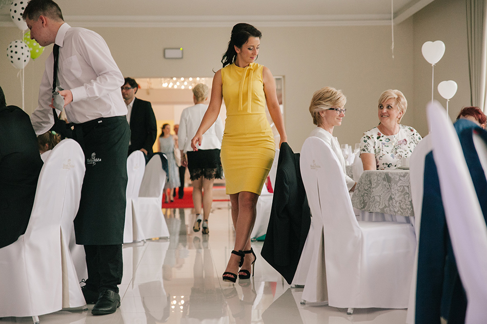 kobieta w żółtym kostiumie przechodzi obok siedzących przy stoliku pań