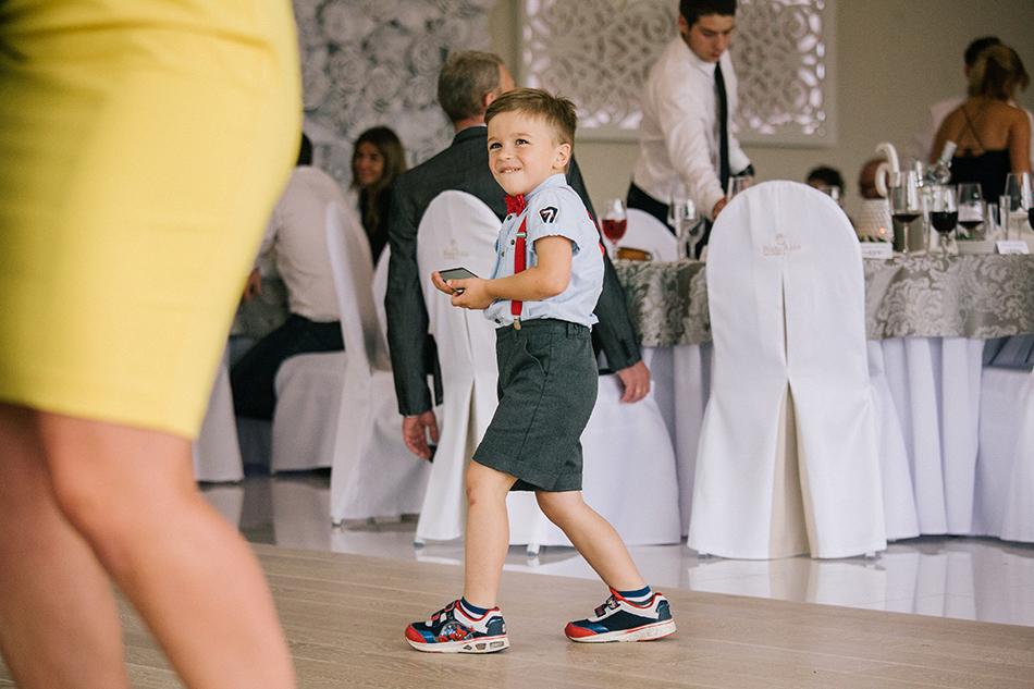 chłopczyk przedzadza się wśród tańczących ludzi