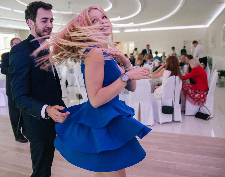 młoda blondynka w niebieskiej sukienki kręci się wokól na parkiecie