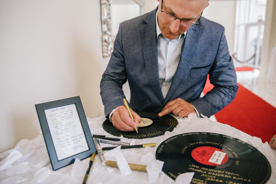 mężczyzna podpisuje się na pamiątkowej płycie winylowej dla pary młodej