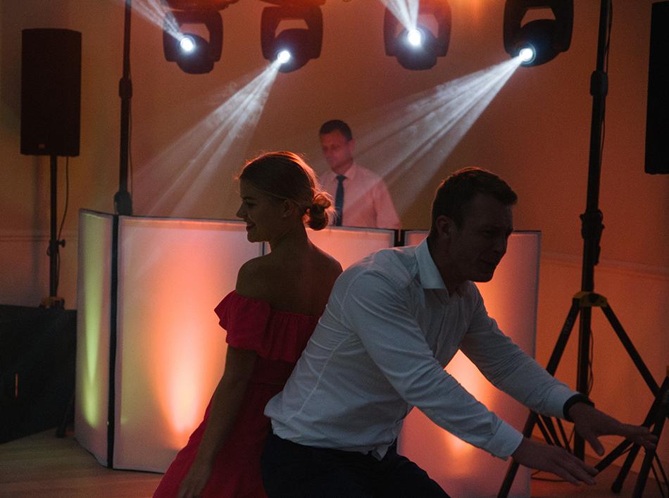 młodzi tańczą w tle widać światła Dj'a