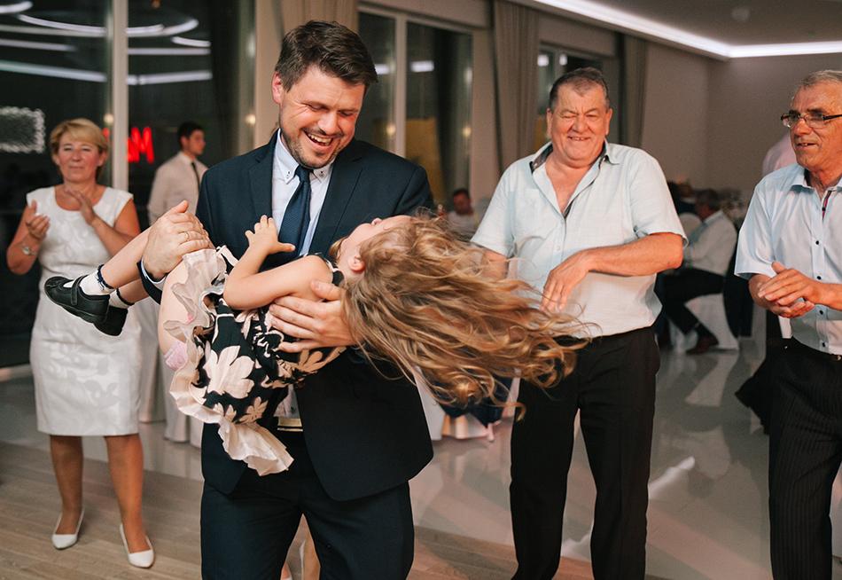 meżczyzna kręci się w kółko w tańcu z małą dziewczynką, jej włosy powiewają