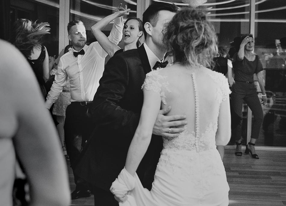 pocałunek pary młodej, w tle bawiący się goście