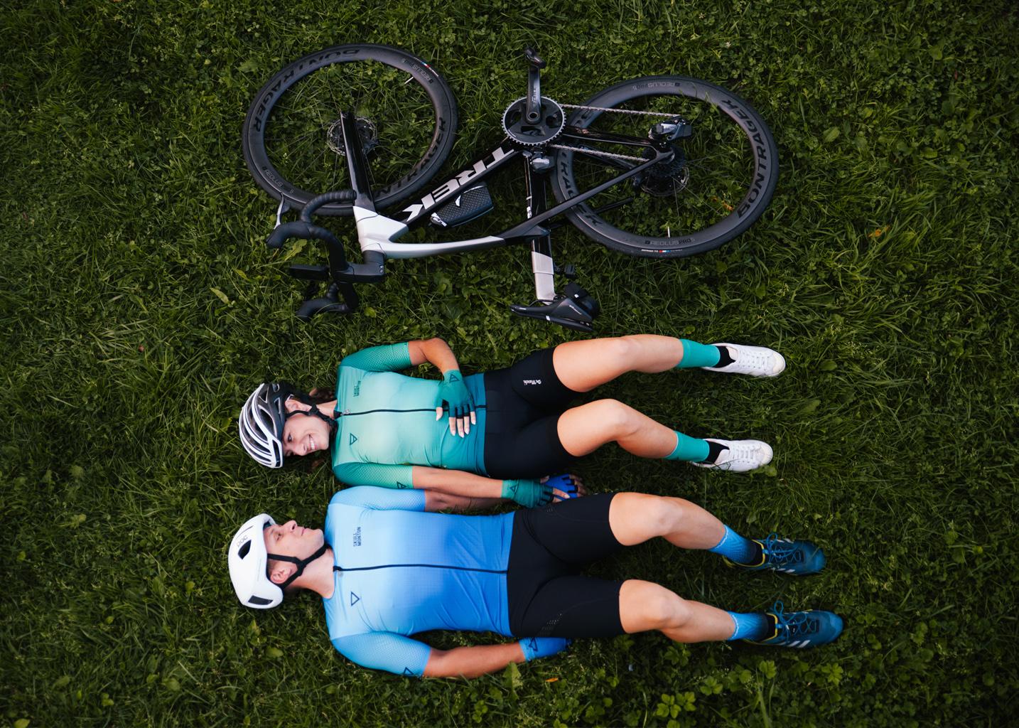 Młodzi rowerzyści leżą na trawie obok swoich rowerów, uśmiechają się do siebie