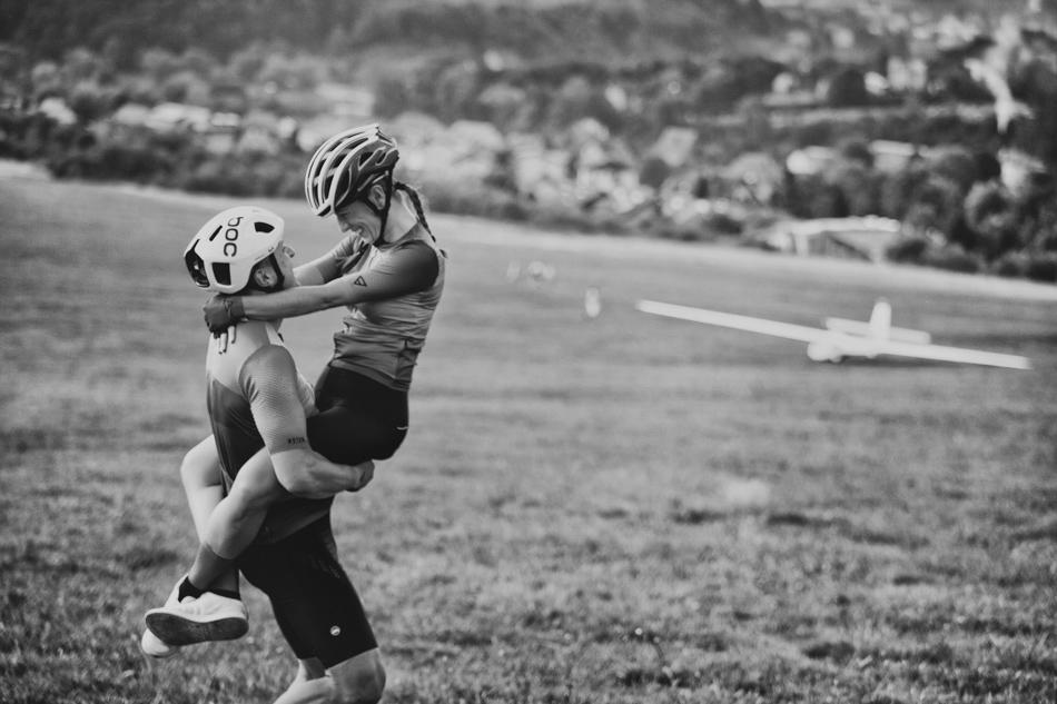 Zakochani sportowcy wygłupiają się ze sobą i śmieją do siebie, on trzyma ja na swoich biodrach, sa objęci, w tle jest szybowiec