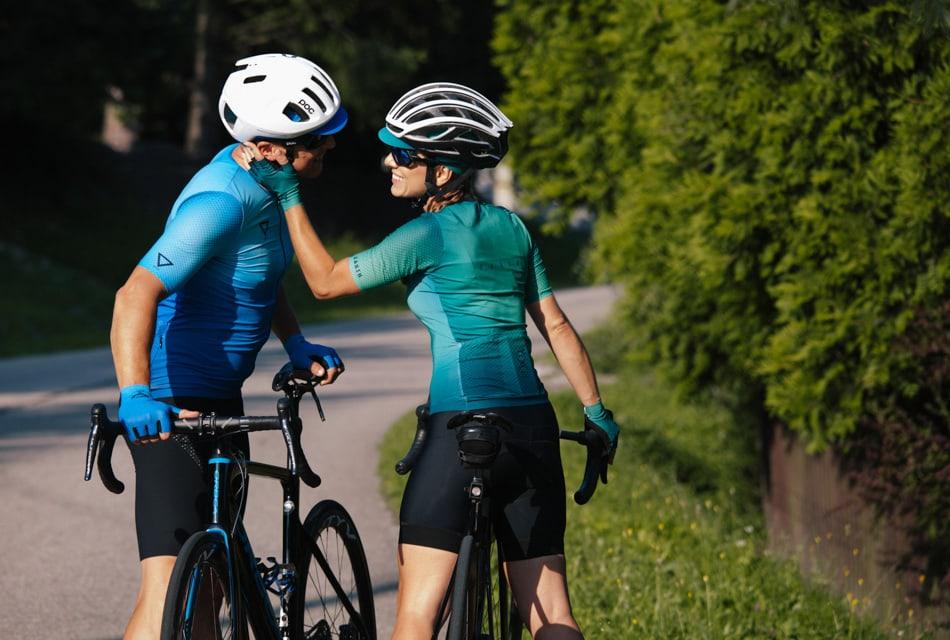 Para rowerzystów, w sportowych strojach patrzy sobie prosto w oczy