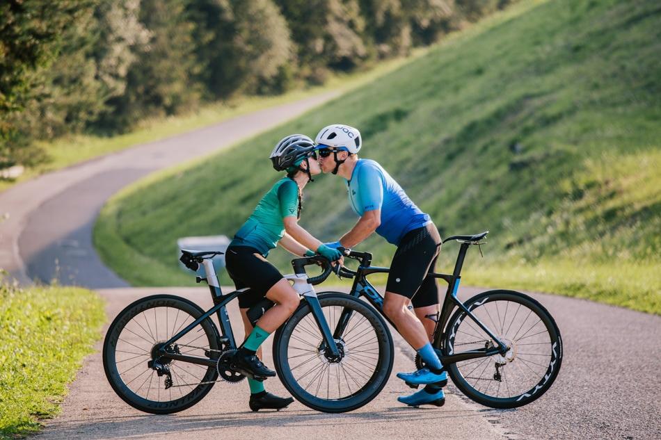 Dziewczyna i Chłopak całują się siedząc na sportowych rowerach szosowych, w tle droga na Górę Żar