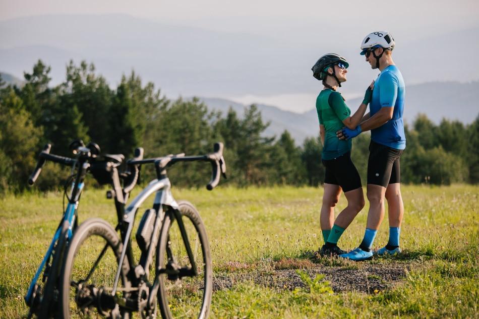 Rowerzyści stoją obok siebie, delikatnie sie dotykając nawzajem, patrzą na siebie, w tle Góry Beskidy