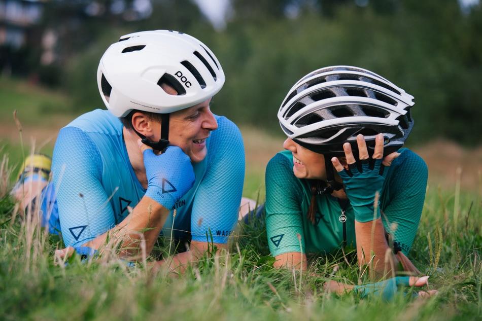 Młodzi Rowerzyści w strojach i kaskach sportowych leżą na trawie i uśmiechają się do siebie