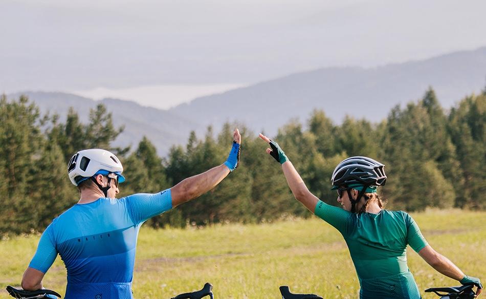 Młodzi rowerzyści przebijają porozumiewawczą piąteczkę, w tle góry