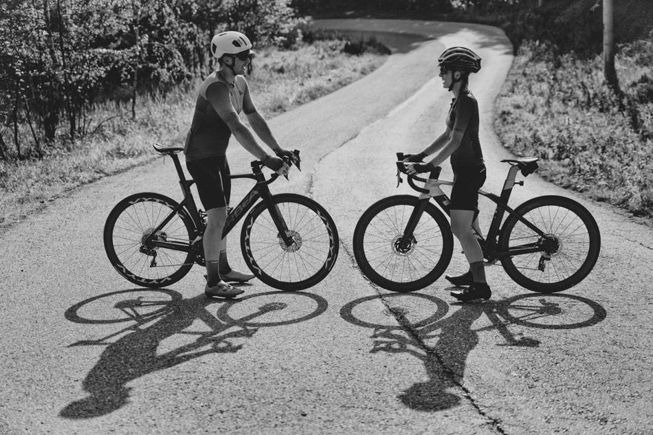 Czarno białe zdjęcie, Kobieta i Mężczyzna na drodze asfaltowej stoją na swoich rowerach, są zwroceni do siebie twarzami, na jezdni odbijaja się ich cienie