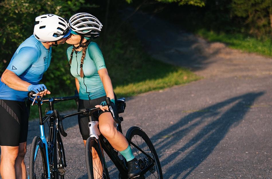 Rowerzyści całują się, są ubrani w proefesjonalne stroje sportowe