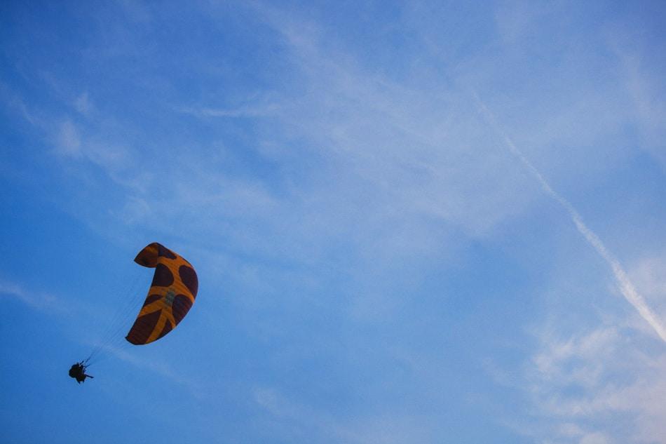 Na niebieskim, słonecznym niebie unosi się spadolotniarz, jest to Góra Żar