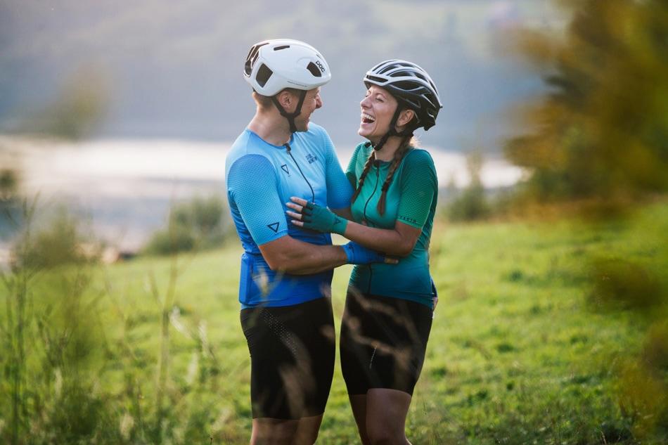 Zakochani Rowerzyści wesoło śmieją się do siebie, są w strojach rowerowych