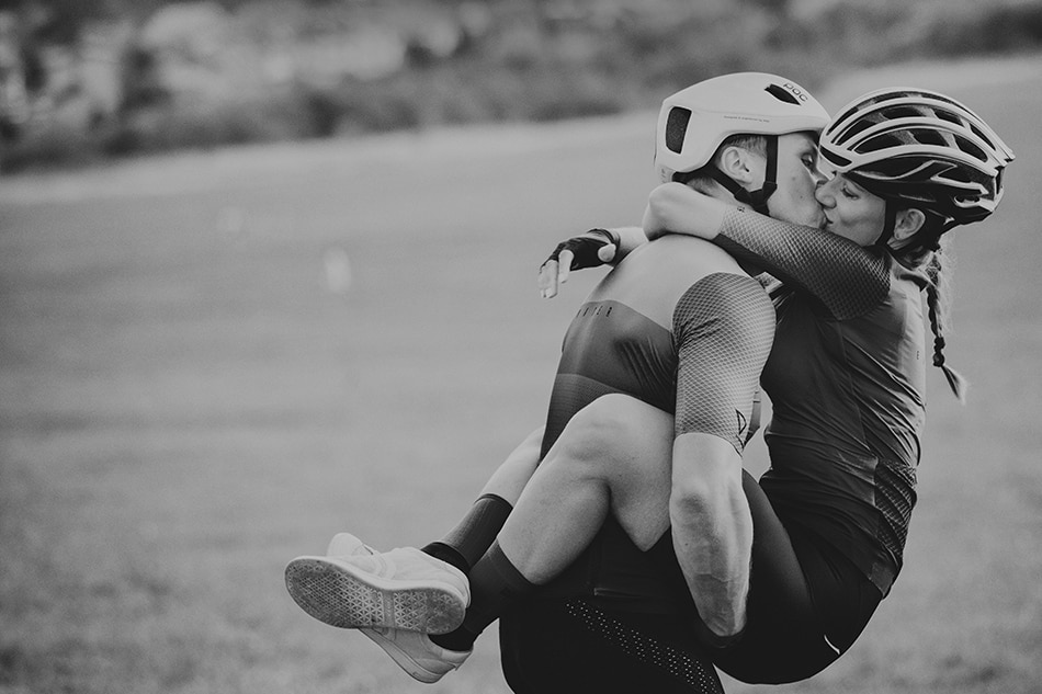 Zakochani sportowcy całuja się, są bardzo przytuleni do siebie, ona oplata jego nogami w pasie