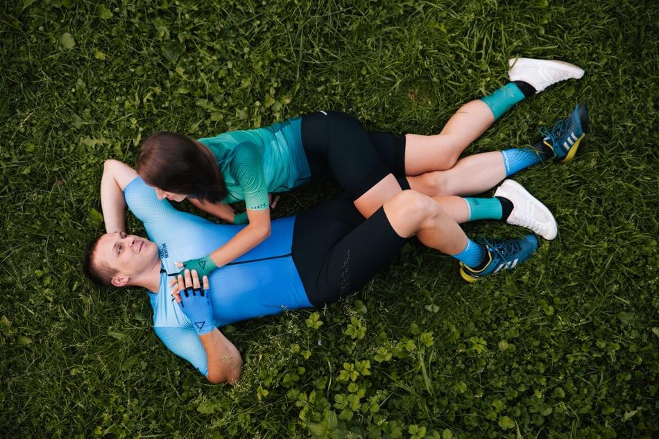 Młodzi Rowerzyści lezą na trawie, patrzą na siebie czule, ona dotyka jego klatki piersiowej