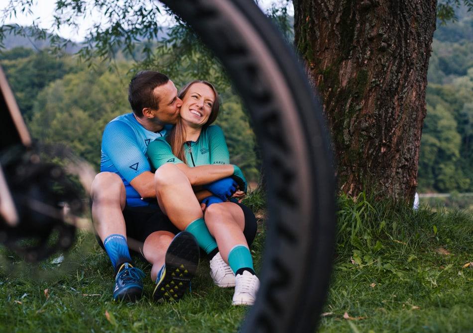 Chłopak całuje swoja Dziewczynę, ona śmieje się, zdjęcie jest zrobione przez koło roweru szosowego