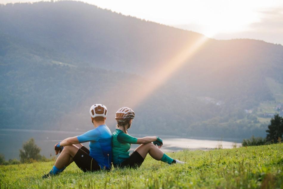 Rowerzyście siedza na łące, obróceni do siebie plecami, patrzą w stronę gór- Beskidów i w stronę słońca
