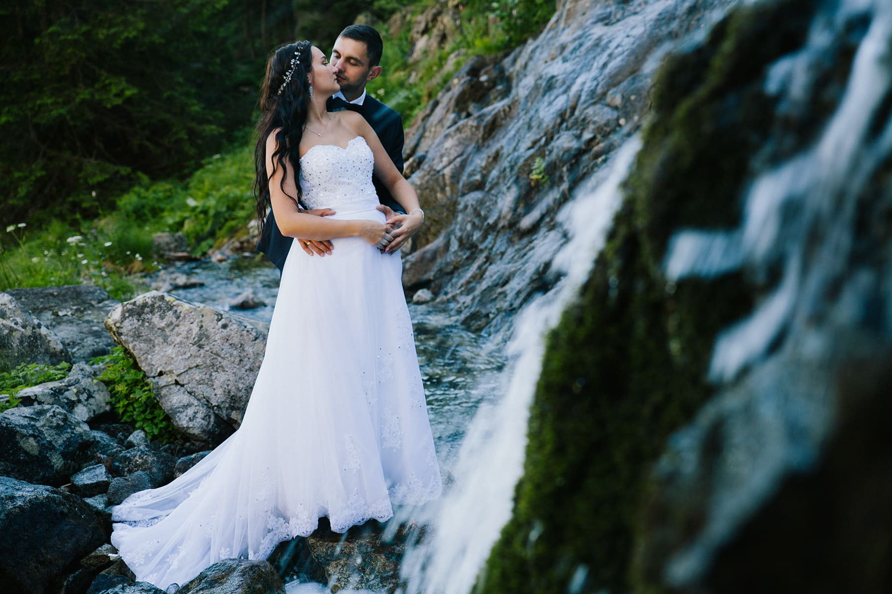 para młoda przytula się do siebie, obok wodospadu
