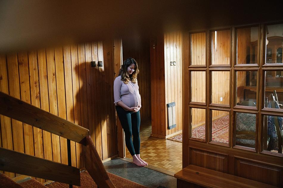 kobieta patrzy na brzuszek, czule go dotyka, jest w swoim drewnianym domu