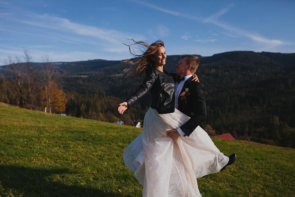 kobieta skacze na swojego partnera, oboje się śmieją